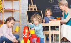 Little boy building a rocket on a carpet in kindergarten