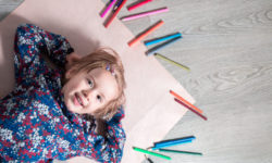 Child lying on the floor on paper looking at the camera near crayons. Little girl painting, drawing. Top view. Creativity concept.
