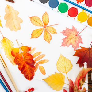 Watercolor painting with autumn leaves, paint, brushes and colorful autumn leaves on wooden background. Top view.