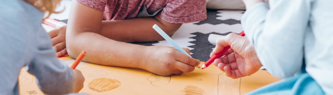 Close-up of group of children drawing together during art classes in kindergarten